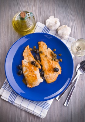 Fish fillet with black olives and capers.