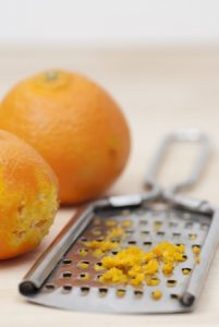 16724845 - grater and citrus zest on wooden kitchen surface.